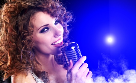 Portrait of a glamorous girl with mike singing song  photo
