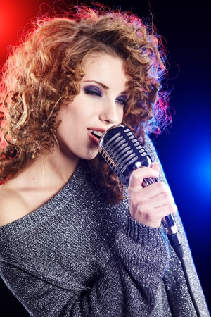 Rock star.Sexy Girl singing in retro mic  photo