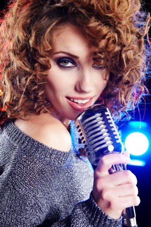 stage performer: Rock star.Sexy Girl singing in retro mic  Stock Photo