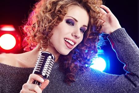 Rock star.Sexy Girl singing in retro mic  photo