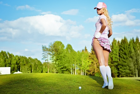 Portrait of an elegant woman playing golf on a green  photo