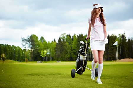 woman golf: A pretty woman golfer on the putting green