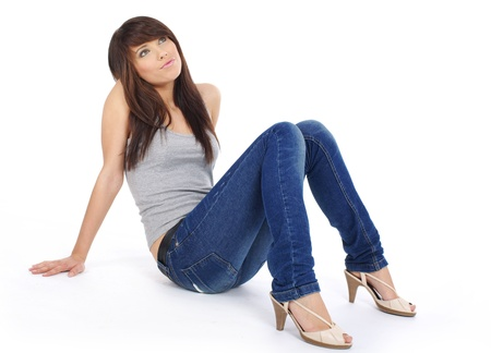 woman sitting floor: Beautiful girl in blue jeans Stock Photo