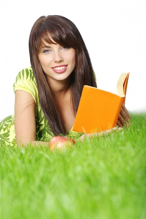 beautiful woman lays on green field and reads book. photo