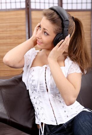 househould: Young  women listening music in headphones