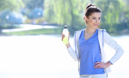 young fitness woman drinking water) photo