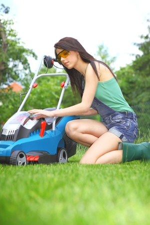 mowing grass: garden work, woman mowing grass with lawnmower
