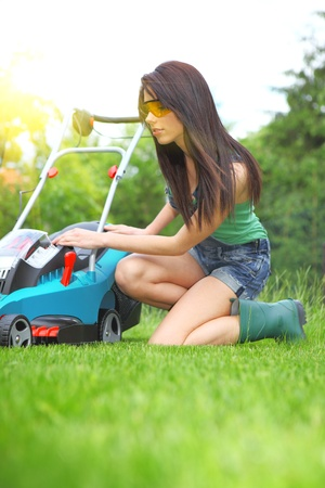 garden work, woman mowing grass with lawnmower photo