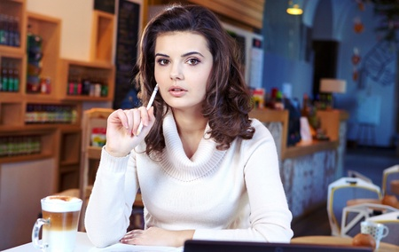 A young attractive business woman sitting in a cafe with a laptop and coffee  photo