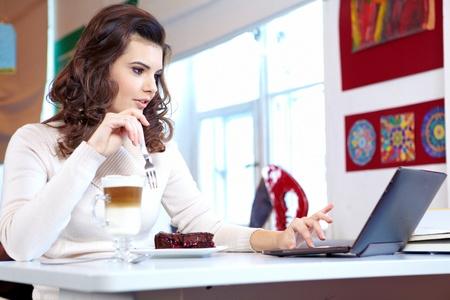 tabla de surf: Una joven mujer de negocios atractiva sentado en un caf� con un ordenador port�til y el caf� Foto de archivo