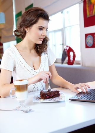 surf shop: A young attractive business woman sitting in a cafe with a laptop and coffee