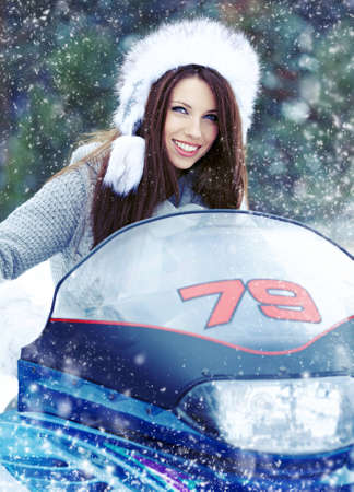 Smiling young woman riding a snowmobile  photo