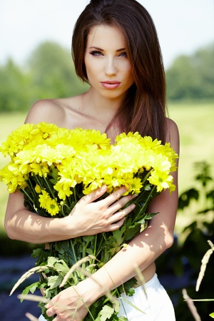 Closeup portrait of cute young girl with yellow flowers smiling outdoors  photo