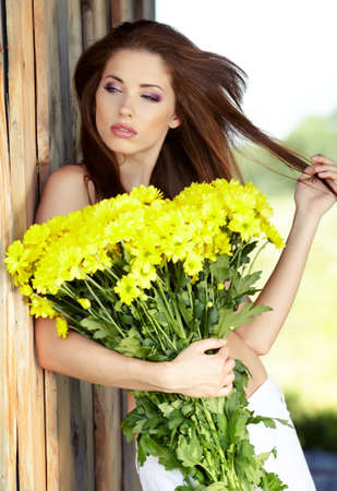Closeup portrait of cute young girl with yellow flowers smiling outdoors  Stock Photo - 12351227