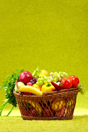basket full of fresh produce  green background photo