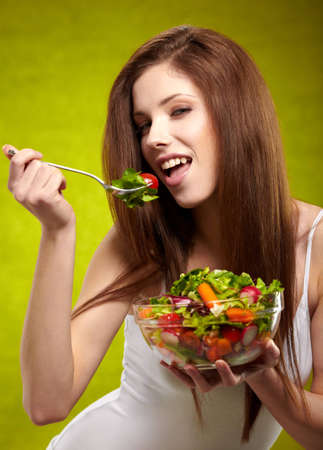 happy healthy woman with salad on green background photo
