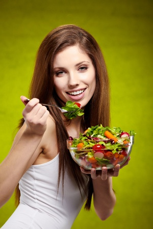 Healthy lifestyle - woman holding vegetable salad on green background Stock Photo - 12501853