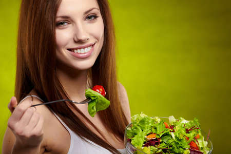 Healthy lifestyle - woman holding vegetable salad on green background  photo