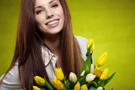 Smiling girl with yellow tulips  green background  photo