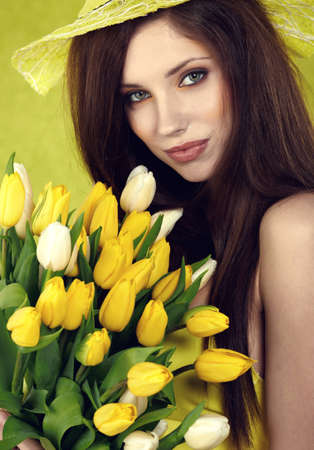 Young  woman hold yellow tulips flower on green  photo