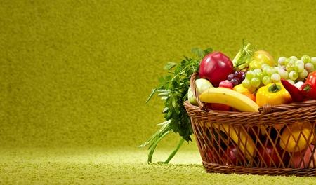 buena salud: Legumbres y hortalizas frescas en la cesta sobre fondo verde