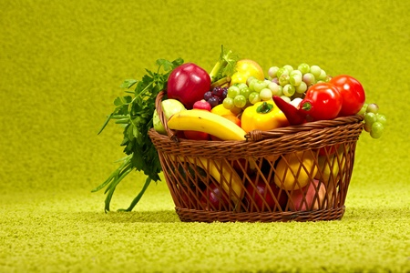 Fresh vegetables in basket  on green background  photo