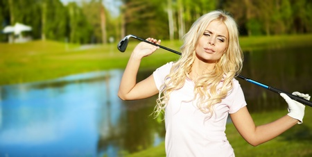 Young blonde  woman with golf equipment photo