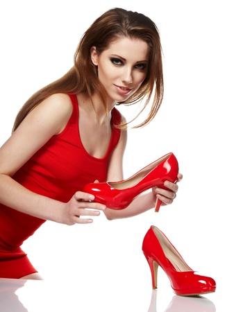 comprando zapatos: Retrato de una mujer joven feliz celebración de un zapato rojo