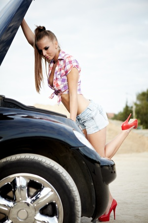 busted: young sexy woman with her broken car