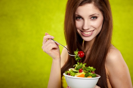 The beautiful cheerful young woman has breakfast salad photo