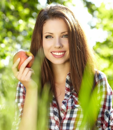 Woman with apple in garden photo