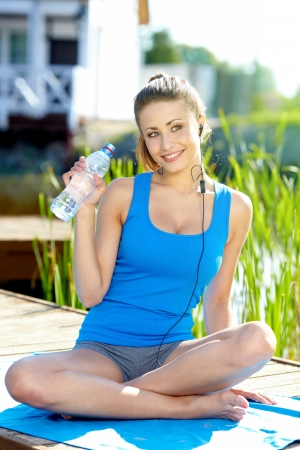 portrait of young woman drinking water against a plants background  photo