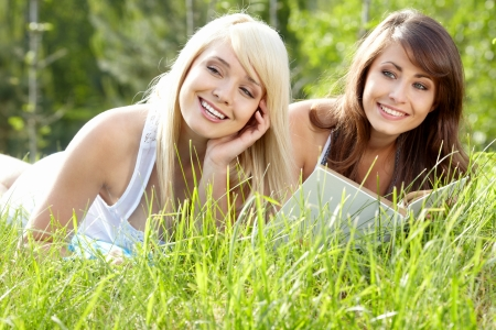sisters sexy: Two young beautiful girls reading book at summer green park