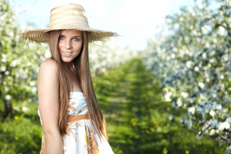 beautiful young woman standing near the apple tree on a warm summer day