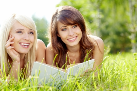 blond haired: Two young beautiful smiling women reading book, sitting on grass at summer green park