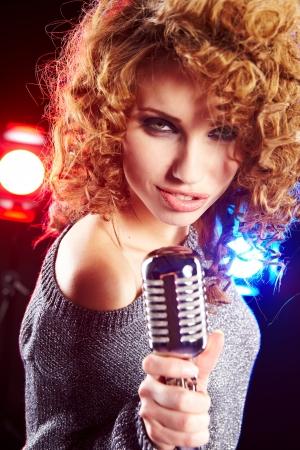 kareoke: woman holding a retro microphone