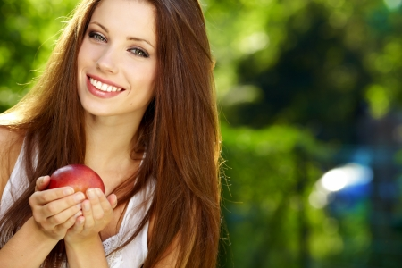 dark haired: portrait  long-haired woman hands red  apple background summer park