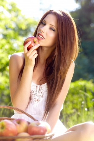 Woman holding apple. Green garden background  photo