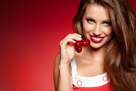 provocative food: picture of cherry and lips over red background Stock Photo