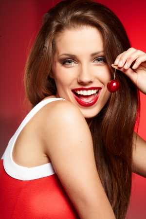 glowing skin: happy woman with cherries over red