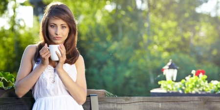 Young woman at  home terrace sipping tea from a cup photo