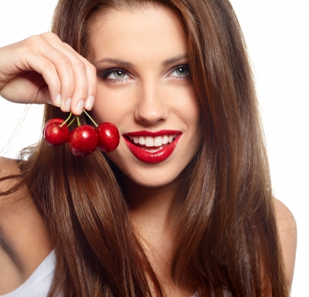 wet lips: brunette holding cherryes, close up, looking at camera Stock Photo