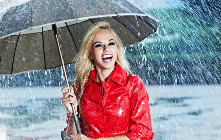 woman with umbrella: Woman in raincoat smiling as she holds umbrella