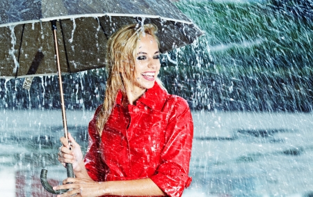rainy season: Beautiful blonde woman holding umbrella out in the rain  Stock Photo