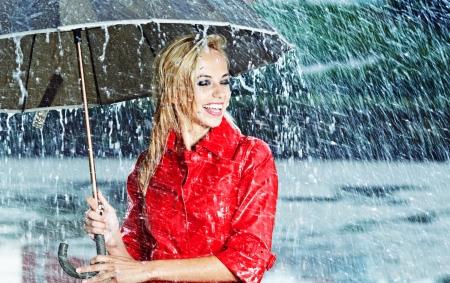 lluvia paraguas: Mujer rubia hermosa que sostiene el paraguas bajo la lluvia