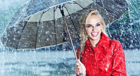 beautiful umbrella: Beautiful blonde woman holding umbrella out in the rain  Stock Photo