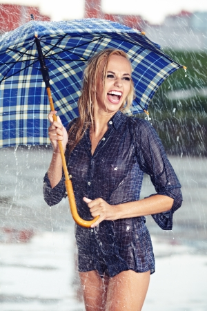 Sexy girl under umbrella watching the rain photo