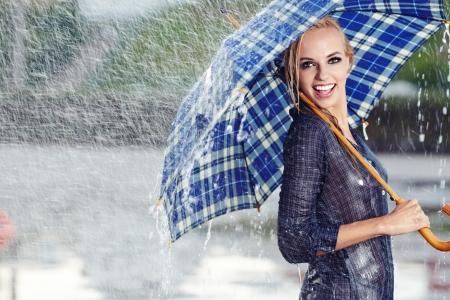sotto la pioggia: Sexy ragazza sotto l'ombrello a guardare la pioggia