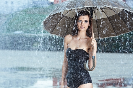 carrying girl: Beautiful  woman holding umbrella out in the rain