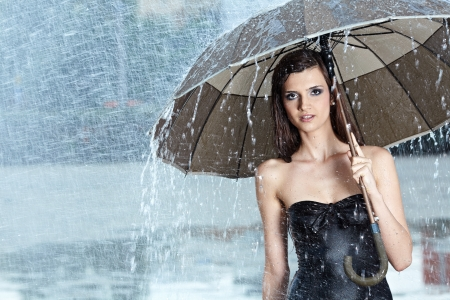 Beautiful  woman holding umbrella out in the rain Stock Photo - 14695532